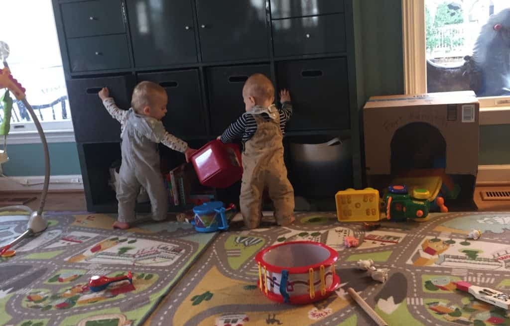 Twins playing by a box fort