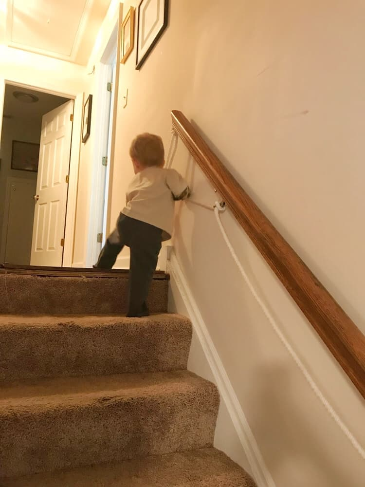 Boy on a stairway with rope railing