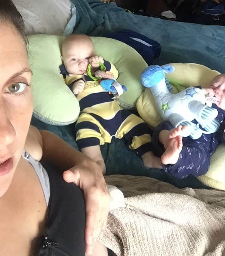 Selfie of woman pumping breast milk with medela and kiinde gear with twin boys watching