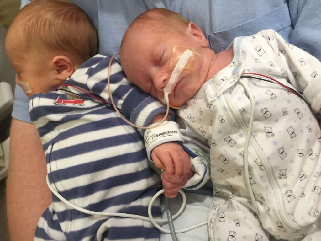 Twin brothers di/di twins holding hands in the nicu