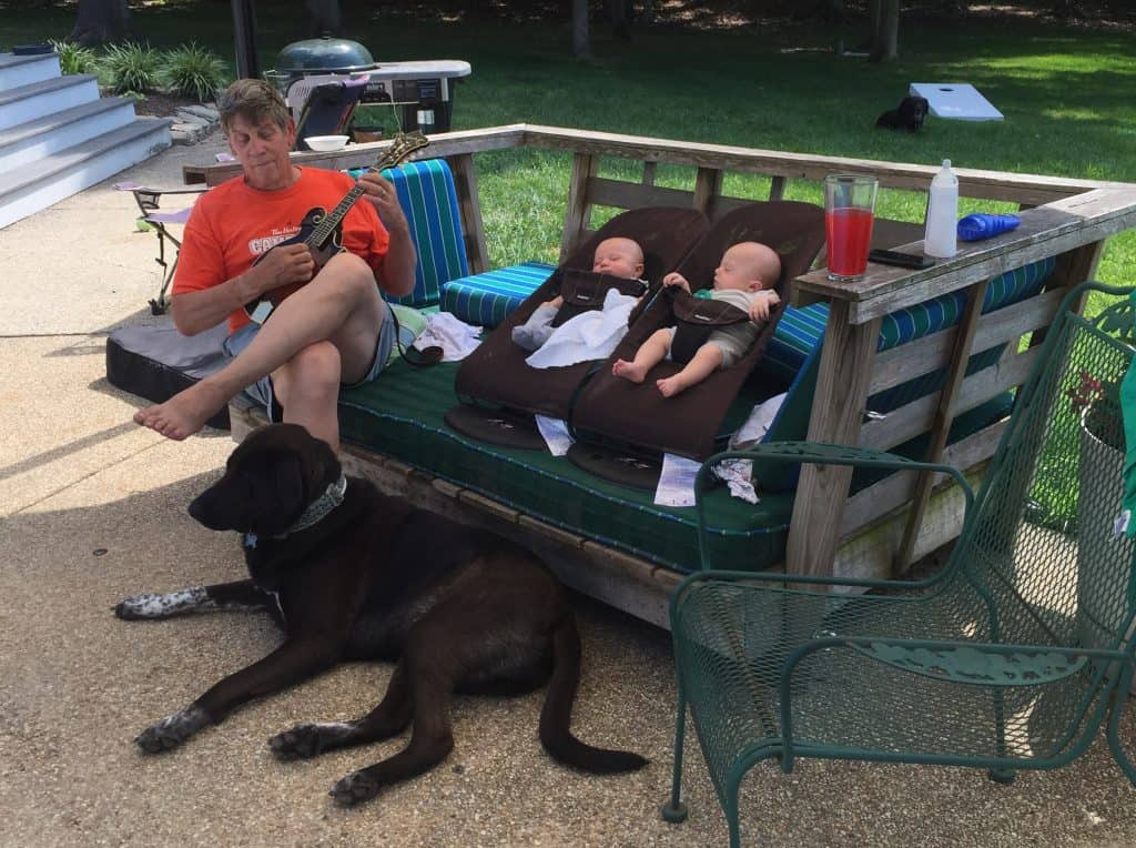 Hank the Big Black dog lying in front of a sofa with twin babies lying in Baby bjorn chairs with grandpa and a mandolin