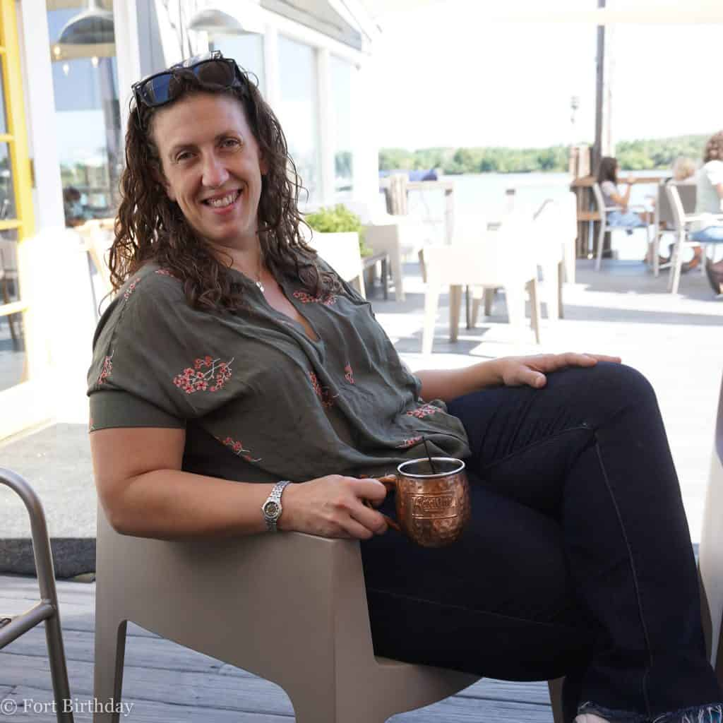 Mommy Blogger relaxing on a dock with an Oxford Mule MomBod Mom jeans