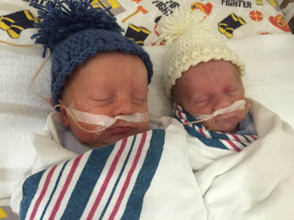 Fraternal Twin boys in the nicu wearing coordinating hats not identical