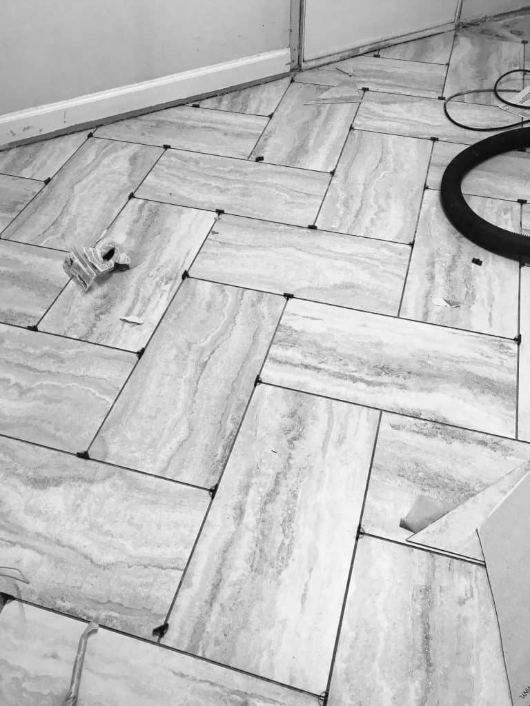 Herringbone vinyl tile floor laid out grey and white gorgeous Mommy Blogger DIY